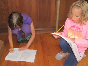 Emma Carpenter edits a piece of writing with another camper last summer.