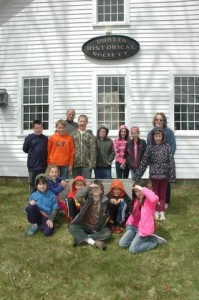 The young students who visited the museum are (standing L-R): Riley Morse, Elias Niemela, Gareth Armstrong, Steven Van Etten, Alexis White, Morgan Wallace, Katelynn Horn and Deborah Bennett. Sitting in front of them are (L-R): Charlie Hall, Daisy Ober, Caleb Cloutier, Nick Parker, Carter Rousseau and Lilly Colon. Photo by Sally Shonk