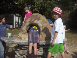 Children apply the finishing touches to their outdoor bread oven.