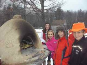 DCS fifth graders roasting our own garden potatoes in our new outdoor bread oven.