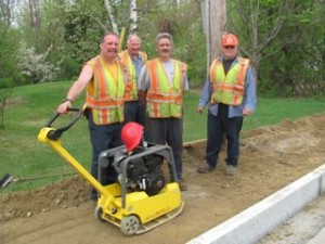 Our road crew (l-r: David Stone, Brian Barden, Mike Howe, and Roger Trempe) were hard at work completing the town sidewalk project along Route 101 (Main Street) in mid-May, the fifth or sixth year of the endeavor. Curbsides are in and the foundation is being readied. This just about wraps up the project. Photo by M. Gurney