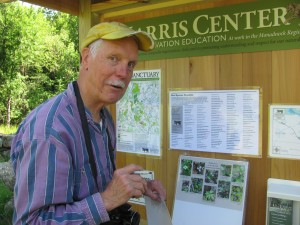 Meade Cadot, former director of the Harris Center, stands at the kiosk to the new trail. He is chekcing off plants and animlas that have already been observed in this newest land acquisition. Photo by Margaret Gurney