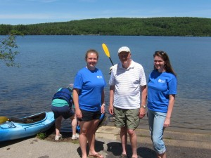 Genna Weidner and Annie Garrett-Larson are returning Lake Hosts from last year, on duty weekends from July 4 through August 23, 9 am to 5 pm. We encourage you to stop by and educate yourselves about the hazards of invasive aquatic plants and animals getting into our lake. Bill Goodwin, their point person, is at center. Photo by Sally Shonk